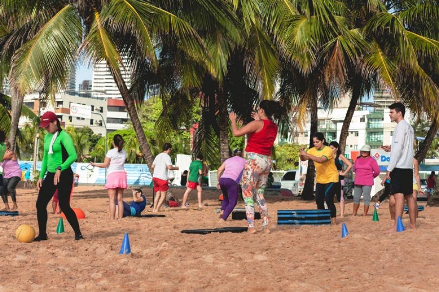 Muito movimento em busca de saúde e qualidade de vida: exercícios físicos na areia da praia